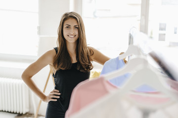 Portrait of smiling young woman in fashion studio