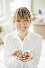 Portrait of smiling woman holding buttons