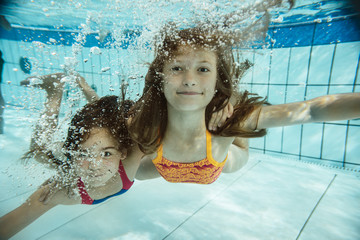 Portrait of two girls swimming under water in swimming pool