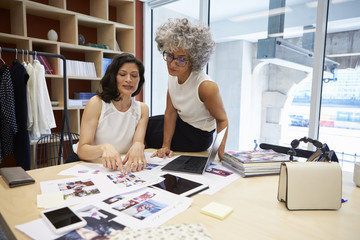 Two female creatives discussing magazine layout in an office