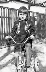 Vintage photo of little girl on old bicycle