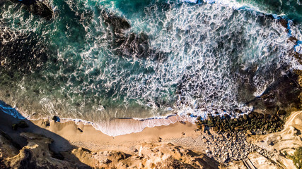 Drone view of waves hitting the shore and beach