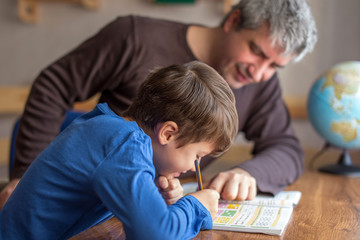 Young little shoolboy solving mathematics homework with father