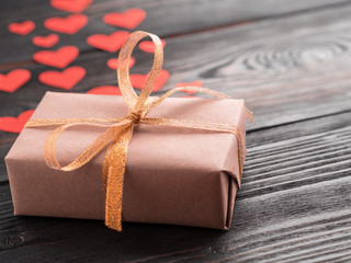 gift box with ribbon and lots of little red hearts on wooden texture dark background, side view