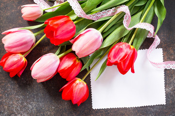 Valentine background or greeting card. Congratulatory sheet of paper with red and пинк tulips on a dark stone background. Free space for your congratulations.