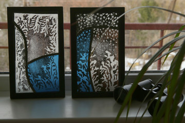 Stained glass with frosty drawing on windowsill. Handmade stained glass graphic pictures.