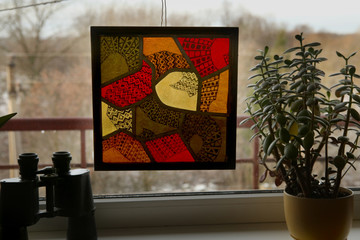 Stained glass with colorful drawing on windowsill. Handmade stained glass graphic picture.