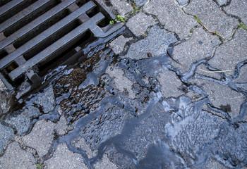 Wasser / Regenwasser fliesst in Kanalisation durch Gullideckel
