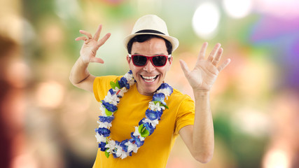 Radiant man celebrates. Man smiling at party. Brazilian celebrating carnaval. He's on his feet. Isolated on colored background..
