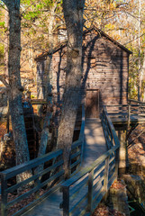 Grist Mill and the wooden bridge in the Stone Mountain Park in sunny autumn day, Georgia, USA
