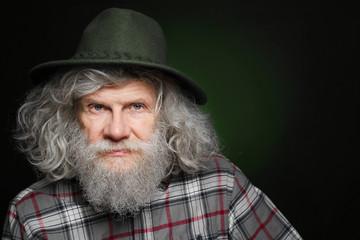 Senior man in hat on dark background