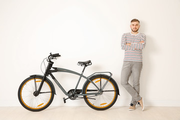 Handsome young hipster man with bicycle near light wall