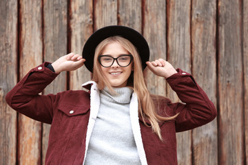 Attractive hipster girl in hat near wooden fence outdoors