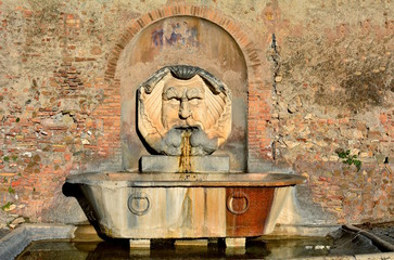 Beautiful fountain in orange gardens in Rome, Italy. Is this wonderful fountain of a giant, grotesque mask, which spits water into a giant, ancient Roman basil.