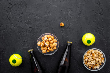 Snacks for watching sport matches and games on TV. Popcorn, rusks near drink and ball on black background top view copyspace