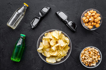 Cinema food. Crisp, popcorn, rusks near glasses on black background top view