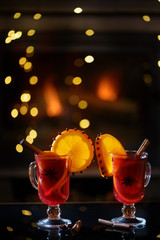 Delicious winter mulled wine with oranges at romantic fireplace with falling stars on background 8