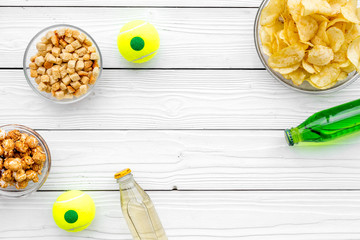 Snacks for watching sport matches and games on TV. Crisps, popcorn, rusks near drink and ball on white wooden background top view copyspace