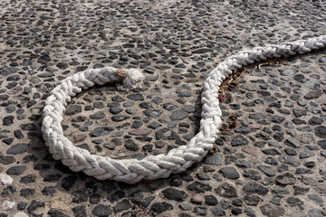 Strong bright rope on the dark stone floor