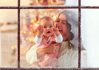 cute infant baby girl in mother hand looking through the window, family winter holidays