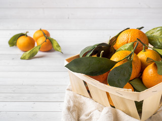 Fresh mandarin or tangerines with stems and leaves on the box on white wooden background