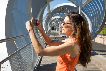 adult woman with orange shirt in summer, taking a photo or video recording with a smartphone, at modern urban footbridge, in Madrid city, Spain, Europe