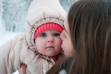 Child girl playing with her mom in the winter forest