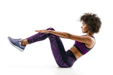 Beautiful young girl doing fitness exercise sit-ups, abs. Photo of african girl in silhouette on...