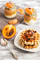 Homemade waffles with cream and pulp tamarillo on a wooden white table. Yogurt with fruit, tangerines, apple puree.