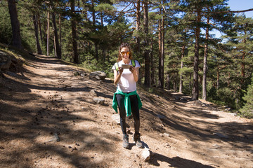 hiking woman with white shirt looking at smartphone to choose the right way, between two paths in forest of Navacerrada mountain, in Guadarrama Natural Park, Madrid, Spain