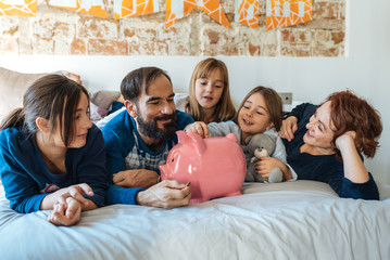 Mature couple relaxed at home in bed with their four little daughters saving money on the piggy bank.