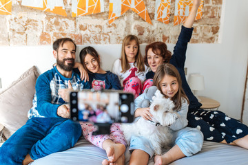 Couple relaxed at home in bed with their three little daughters on the mobile phone taking a family selfie.