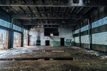 Ruined interiors of abandoned industrial hall. Charred walls