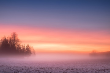 Foggy and colorful sunset with peaceful landscape at winter evening in Finland