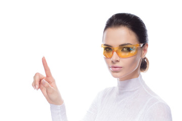Brunette model, attractive girl wearing yellow glasses, index finger up against white background