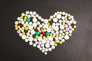 The heart made of pills on dark background