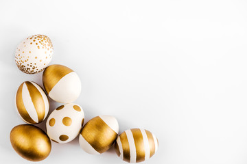 Top view of easter eggs colored with golden paint. Various striped and dotted designs. White...