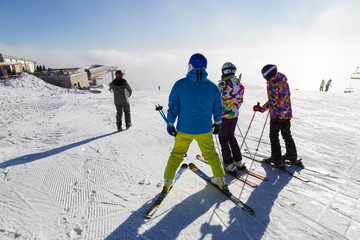 People and ski. Skiers on ski snow-covered slope on mountain top