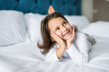 Adorable smiling little girl with smile waked up in her bed