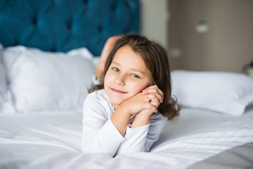 Portrait of beautiful girl, dreaming in bed. Beauty little girl in bed at home.