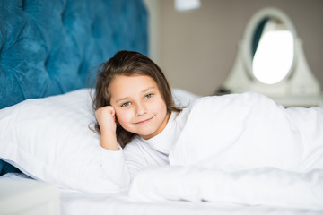 Close-up portrait of beautiful little kid lying on bed with hand under pillow, looking at camera