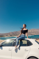 Happy young girl sitting on the white car