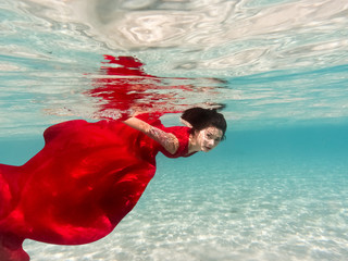 Underwater girl swimming in a scarlet dress