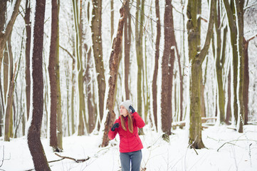 Beautiful girl walking in the winter forest