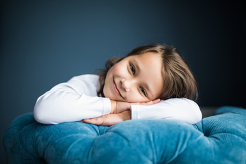 Little young kid sitting on chair hands on face with beauty smile look at camera at her room at home