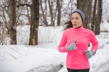 Winter sport fitness girl running in snow wearing wind jacket, gloves, headband and smartwatch. Asian woman healthy and active lifestyle training outside during the cold weather winter season.