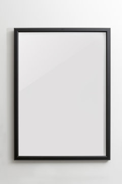 Wooden black empty frame on white wall