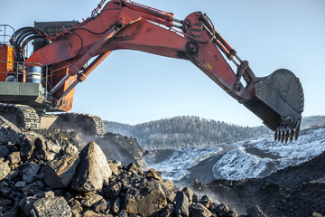 Big yellow dump truck and excavator in coal mine at sunrise