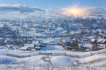Rural alpine winter landscape with fence and path