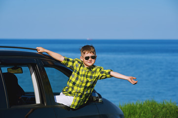 a child looks out the car window . Gay boy enjoys a trip to the sea